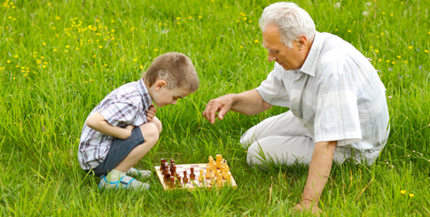 Older man teaching boy chess